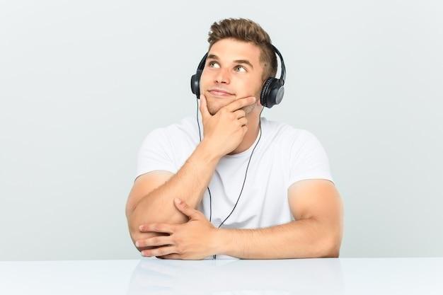 Junger mann, der musik mit kopfhörern hört, die mit zweifelhaftem und skeptischem ausdruck seitwärts schauen.