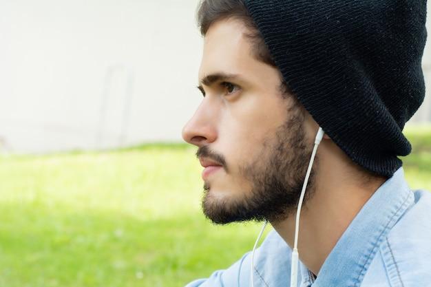 Junger mann, der musik mit kopfhörern hört