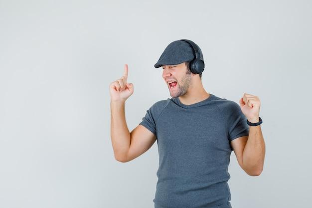 Junger mann, der musik mit kopfhörern im t-shirt, in der kappe genießt und munter, vorderansicht schaut.