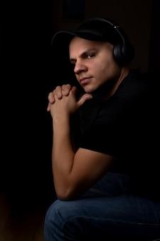 Junger mann, der musik mit seinen kopfhörern in der dunkelheit hört