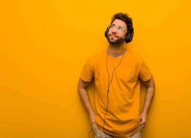 Junger mann, der musik träumt vom erreichen von zielen und von zwecken hört
