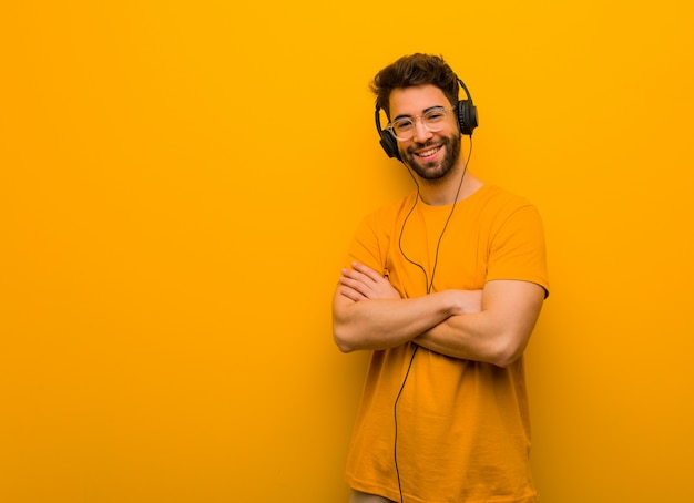 Junger mann, der musiküberfahrtarme, lächelnd und entspannt hört