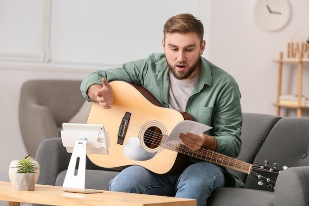 Junger mann, der musikunterricht online zu hause nimmt