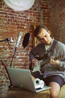 Junger mann, der musikvideoblog-hauptstunde aufzeichnet, gitarre spielt oder broadcast-internet-tutorial macht, während er im loft-arbeitsplatz oder zu hause sitzt. konzept von hobby, musik, kunst und kreation.