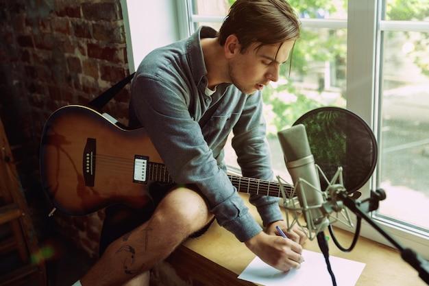 Junger mann, der musikvideoblog, hauptstunde oder lied aufzeichnet, gitarre spielt oder internet-tutorial macht, während er im loft-arbeitsplatz oder zu hause sitzt