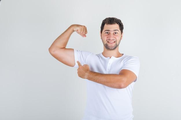Junger mann, der muskel mit finger im weißen t-shirt zeigt und stark schaut