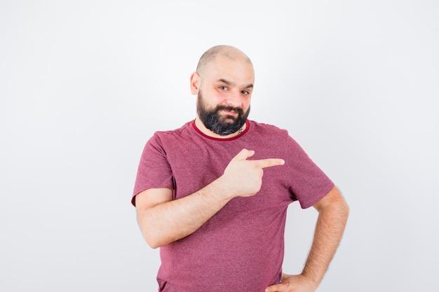 Junger mann, der nach rechts zeigt, während er die hand in rosa t-shirt an der taille hält und optimistisch aussieht, vorderansicht.