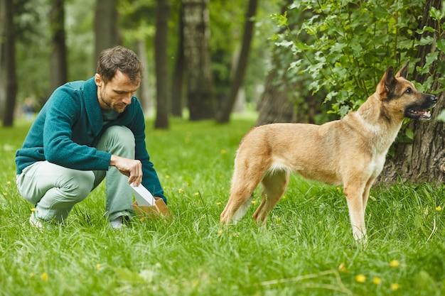 Junger mann, der nach seinem hund vom gras aufräumt, während sie im wald gehen