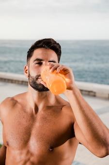 Junger mann, der nach training im freien hydratisiert