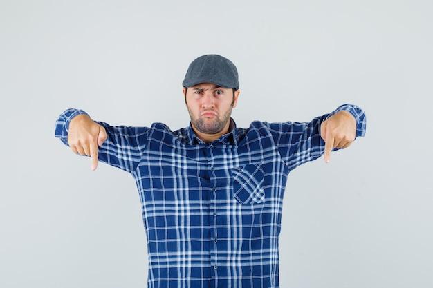 Junger mann, der nach unten zeigt, während er in hemd, mütze die stirn runzelt und ernst aussieht. vorderansicht.