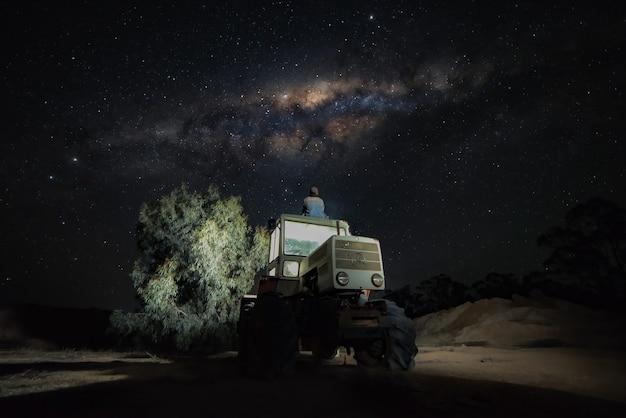 Junger mann, der nachts auf dem dach des traktors sitzt und die milchstraße beobachtet. traveller-konzept