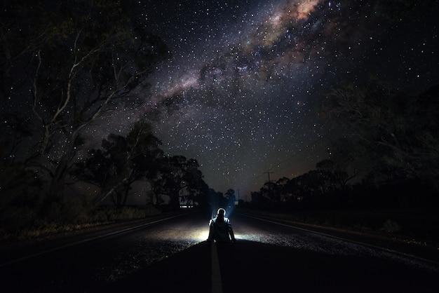 Junger mann, der nachts auf der autobahn sitzt und die milchstraße beobachtet. konzept der reise- und astrofotografie