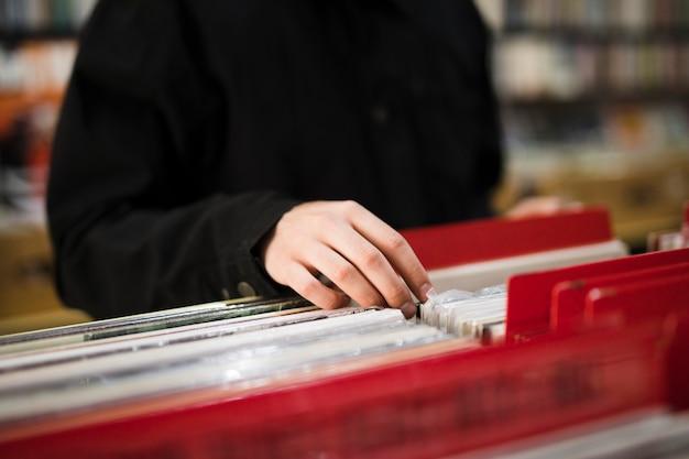 Junger mann der nahaufnahme, der nach vinyls im speicher sucht