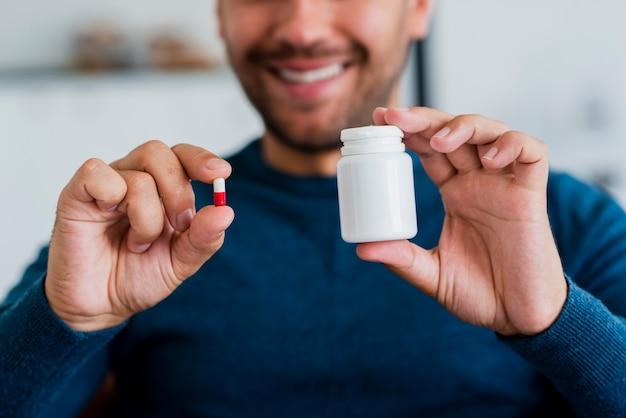 Junger mann der nahaufnahme, der pille und pillenempfänger hält
