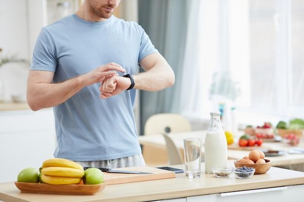 Junger mann, der nahe beim küchentisch mit essen steht und die zeit überprüft, die er stundenweise isst