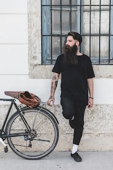 Junger mann, der nahe dem fahrrad weg schaut steht