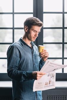Junger mann, der nahe dem fenster hält wegwerfbare kaffeetasse-lesezeitung steht