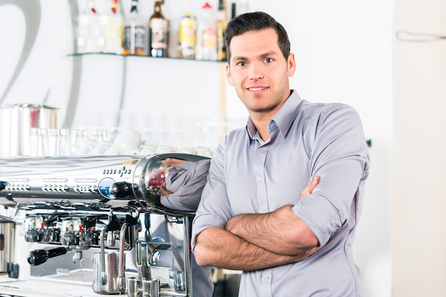 Junger mann, der nahe einer modernen automatischen kaffeemaschine aufwirft