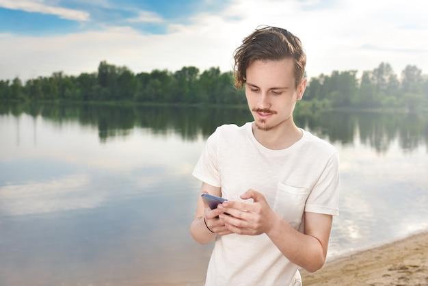 Junger mann, der nahe schöner bucht geht, telefon und kopfhörer benutzt, um mit freunden zu kommunizieren