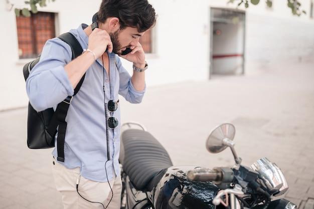 Junger mann, der nahes motorrad steht