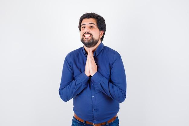 Junger mann, der namaste-geste im königsblauen hemd zeigt und dankbar aussieht. vorderansicht.
