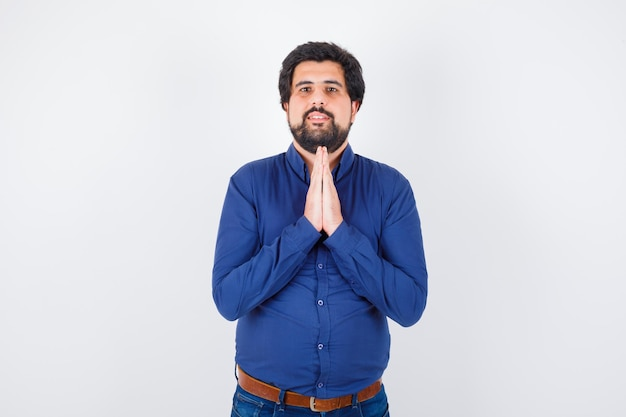 Junger mann, der namaste-geste in der vorderansicht des königlichen blauen hemdes zeigt.