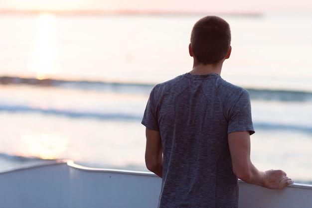 Junger mann, der neben meer meditiert