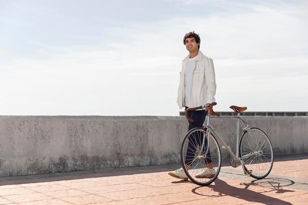 Junger mann, der neben seinem fahrrad aufwirft