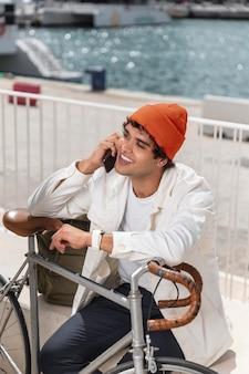 Junger mann, der neben seinem fahrrad mit dem telefon spricht