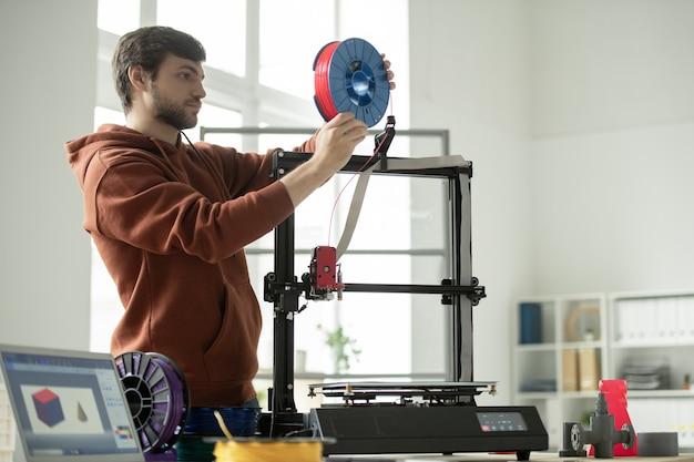 Junger mann, der neue spule mit rotem filament in 3d-drucker setzt, während geometrische figuren drucken