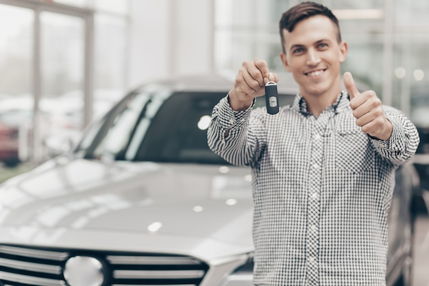 Junger mann, der neues auto an der verkaufsstelle kauft