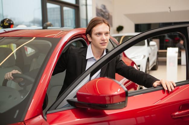 Junger mann, der neues auto wählt, um im autohaus zu kaufen