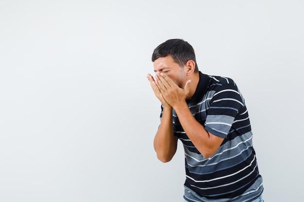 Junger mann, der niest und grippe im t-shirt hat und krank aussieht. vorderansicht.