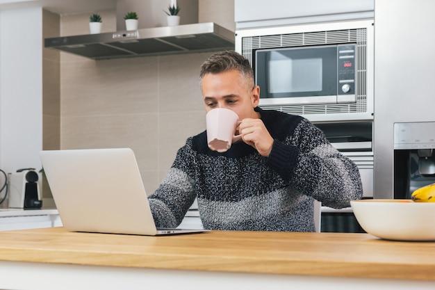Junger mann, der notizbuch beim frühstück, lesen, schreiben von e-mail oder online-sitzen in der modernen küche verwendet