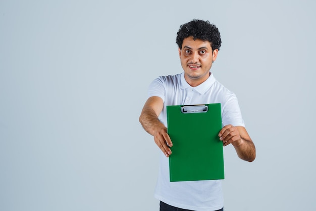 Junger mann, der notizbuch im weißen t-shirt und in den jeans hält und glücklich schaut, vorderansicht.