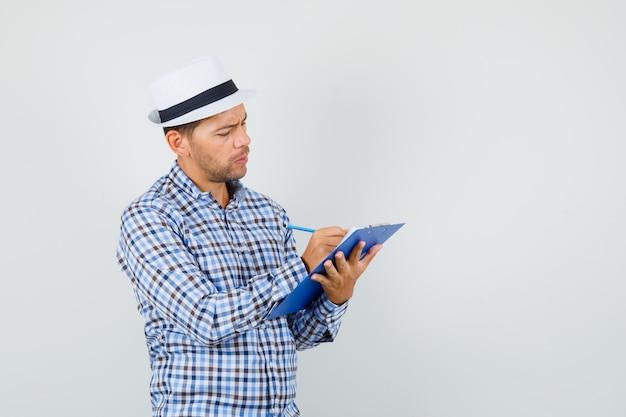 Junger mann, der notizen auf zwischenablage im karierten hemd macht