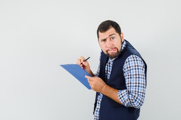 Junger mann, der notizen auf zwischenablage in hemd, weste macht und nachdenklich aussieht.