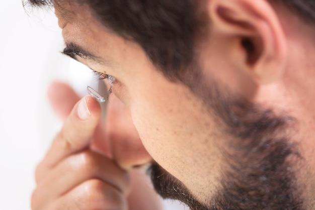 Junger mann, der oben kontaktlinse in sein linkes auge, abschluss einsetzt