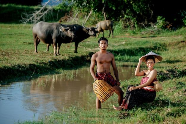 Junger mann, der oben ohne steht und bambus-fangfalle hält, um fisch zum kochen mit einer schönen frau zu fangen, die in der nähe des sumpfes sitzt?