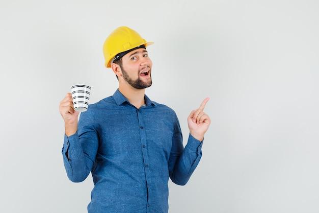 Junger mann, der oben zeigt, tasse kaffee im hemd, im helm hält und glücklich schaut. vorderansicht.