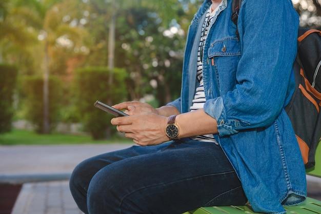 Junger mann, der öffentlich park im park im herbst sitzt