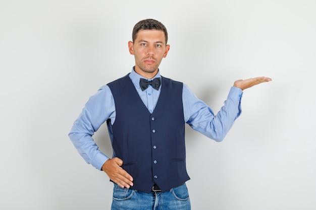 Junger mann, der offene handfläche mit hand auf taille im anzug, jeans hält