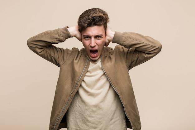 Junger mann, der ohren einer braunen jackenbedeckung mit den händen versuchen, nicht zu lauten ton zu hören trägt.
