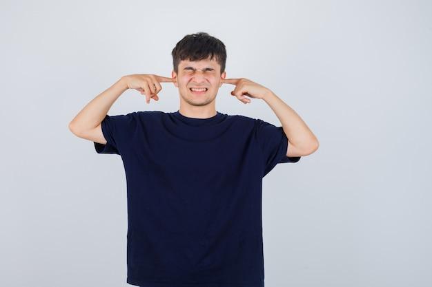 Junger mann, der ohren mit den fingern im schwarzen t-shirt verstopft und genervte vorderansicht schaut.