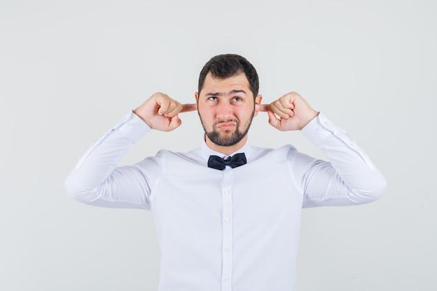 Junger mann, der ohren mit den fingern im weißen hemd verstopft und gelangweilt, vorderansicht schaut.