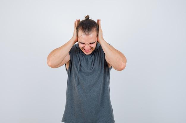 Junger mann, der ohren mit handflächen im kapuzenpulli bedeckt und aggressive vorderansicht schaut.