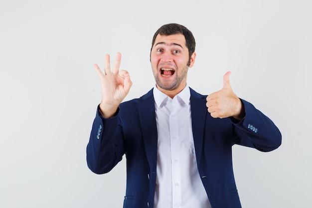 Junger mann, der ok geste mit daumen oben in hemd und jacke zeigt und glücklich schaut