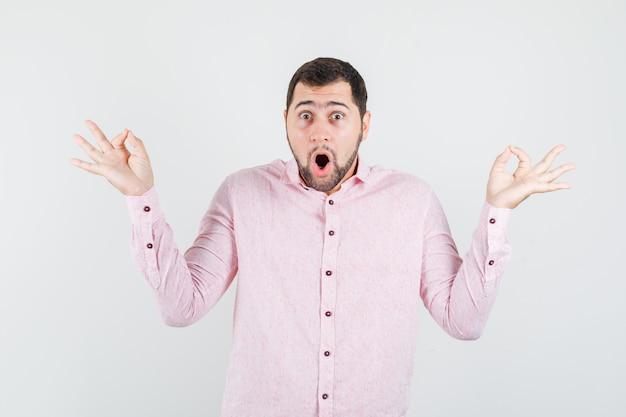 Junger mann, der ok zeichen im rosa hemd zeigt und verwundert schaut