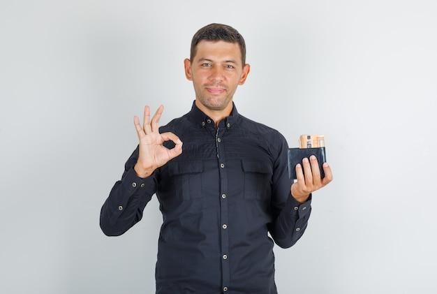 Junger mann, der ok zeichen mit brieftasche im schwarzen hemd tut und glücklich schaut