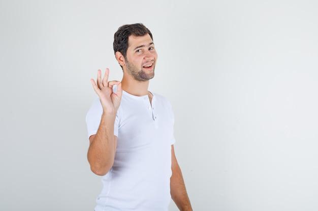 Junger mann, der ok zeichen tut und im weißen t-shirt lächelt